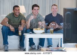 man watching tv holding beer and remote side view stock photo multi ethnic men watching sports on television stock photo