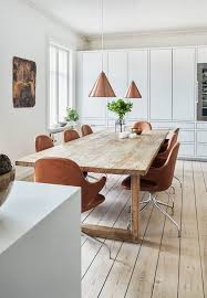 bright dining room featuring a large wooden plank table brown leather dining chairs and pendants in copper
