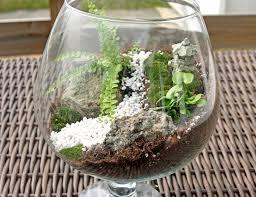 Glass fishbowl or terrarium  Tan and white aquarium gravel  Small  decorative rocks  Living moss  Aquarium temple ornament