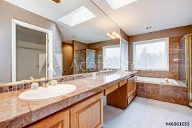 large luxury bathroom with red granite countertops and tub