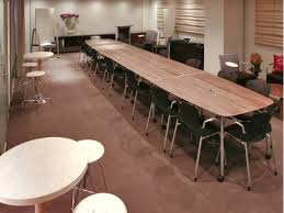 four mobile intersect tables pushed together to create one long conference table surrounded by black caper