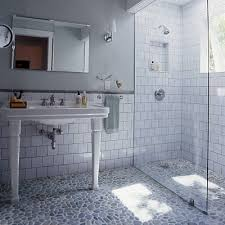 old style subway tile shower with modern glass door and wall and pebble floor