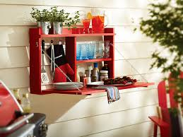 red outdoor buffet cabinet open and hanging on a wall outside