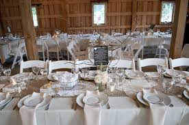 rustic burlap wedding decorations with white flowers in glass vases and small candles on long