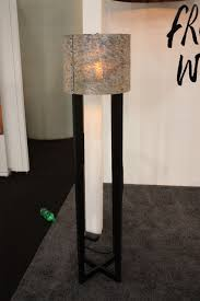 in a more traditional style with a rustic fiber shade this wooden floor lamp would