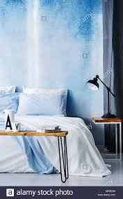 cozy blue black bedroom. Black Lamp On Wooden Table Next To A White Bed Against Blue Wall In Cozy  Bedroom Interior Black I