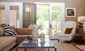 Chic, modern living room with wall of French doors, tan walls paint color,  beige velvet sofa with chaise lounge, zebra pillow, white tufted chair, ...