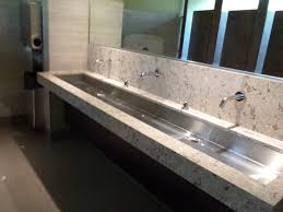 overly long marble steel trough sink two faucets under mirrored medicine cabinet elegant homes
