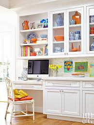 kitchen with built in office glass door cabinets with orange and blue and white accessories