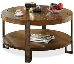 this exquisite round cocktail table beautifully combines distressed woodwork with metal legs and crossing straps round elegant round coffee