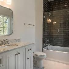 drop in tub and shower combo with black brick tiles