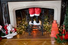 Santa's pants and boots coming down the chimney with Christmas decorations  around Stock Photo - 5373730