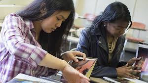 journalism major temple university klein college of media and two female students looking through books in a classroom