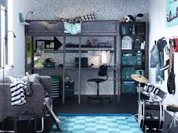 a loft bed with desk underneath and drum kit in a blue dark grey and
