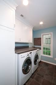 Painted Cabinets, Laminate Countertops, And Porcelain Tile Floor In This Laundry  Room Designed By