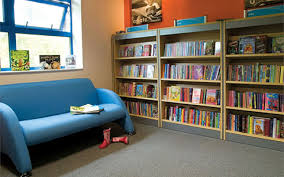 primary school library shelving with a blue sofa infront of the shelving