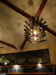 gorgeous refined wine bottle chandelier idea installed on the ceiling beneath exposed wooden beams with iron