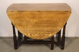 an antique georgian style victorian era oak dining table the polished blonde oak top with two drop leaf extensions these are hinged and open to form a