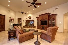 ceiling fan for living room. traditional living room with lancaster leather sofa, built-in bookshelf, dark wood entertainment ceiling fan for