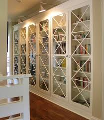these x motif custom designed glass doors along with library lighting give these bookcases an inimitable