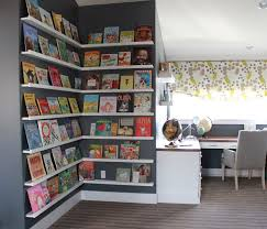 fantastic kids homework room with stacked book ledges wrapping around walls next to l shaped built in desk with wood top paired with gray desk chair placed