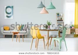 modern colorful chairs at dining table under pastel ls in living room interior with pillows on