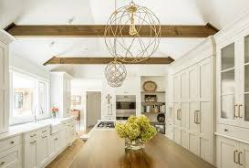 stunning white kitchen with brass accents features a vaulted ceiling with wood beams