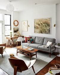 living room desks furniture: our brooklyn apartment light grays and whites really brighten up this room stunning artwork behind this sofa loving the curves on the chairs