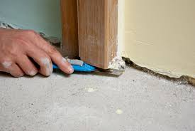 man cutting bottom of door frame