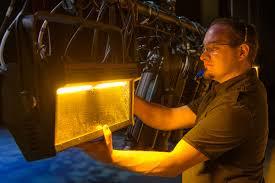 lighting technician. A Lighting Technician Positions Light Ahead Of Show.