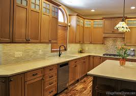 quartersawn oak cabinetry by dura supreme paired with a natural acacia floor natural stone tile