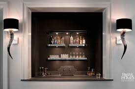 amazing wet bar features walls painted matte black lined with chunky mirrored floating shelves with lighting filled with libations over honed black
