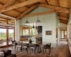 austin texas farmhouse with white chandeliers dining room and exposed beams trusses vaulted ceilings
