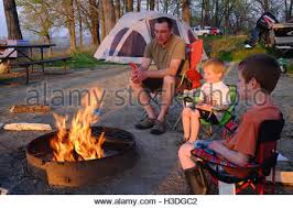 camping in the woods with a fire.  Camping A Man Sits With His Two Sons On Camp Chairs Around A Wood Fire At For Camping In The Woods With Fire I