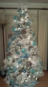 Snow white flocked Christmas tree decorated with aqua blue silver and snow  vine balls.