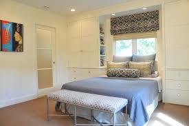 elegant mirrored nightstands in bedroom contemporary with overhead storage next to glass bedroom door alongside storage around window and built in wardrobe