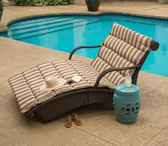 outdoor patio lounge chairs with brown and white cushions and blue table beside the chair
