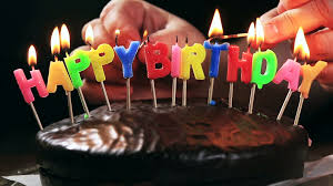 lighted candles on a happy birthday cake candles with the words happy birthday on a chocolate cake hand lights a candle happy birthday
