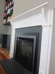 a reclaimed mantel was installed in a new living room renovation to make it look like