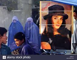afghan women cladding in burqa walk past a poster of n afghan women cladding in burqa walk past a poster of n actress preity on display at