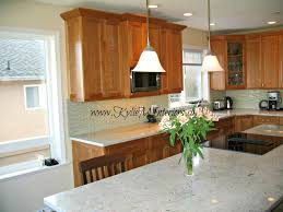 how high to hang pendants or lights over an island or peninsula shown in a cherry kitchen with granit and soft green glass backsplash
