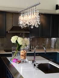 contemporary kitchen features linear crystal chandelier illuminating stainless steel framed island fitted with single bowl sink and modern gooseneck faucet