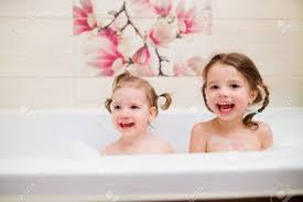 Two Cute Little Girls Having Bath With Bubbles In Bathtub Stock ...