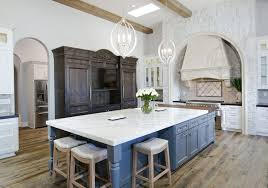 kitchen with white cabinets and large dark blue island and bianco venatino marble countertops