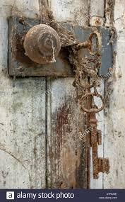 old key in door lock covered in spider webs
