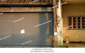 dirty vintage roller shutter door with blank paper note old abandoned house for in