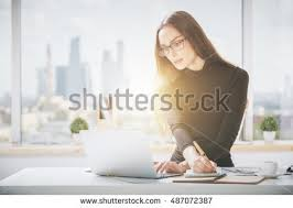 beautiful bright office. portrait of beautiful young businesswoman working on project in bright office with panoramic city view and