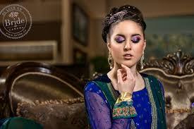 bold purple eye makeup on stani bride wearing blue and gold lehenga and green tta