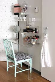 saving very small bedroom spaces with corner clear acrylic console makeup table with floating wall mounted makeup storage and vintage chair with fabric
