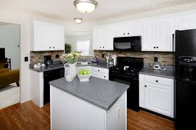 here are white kitchen cabinets with gray countertops and black appliances